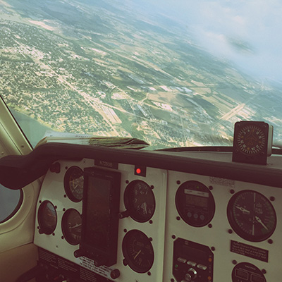 view of a planes dashboard and windshield while flying above a small town